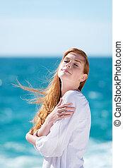 Woman enjoying the sunshine at the beach
