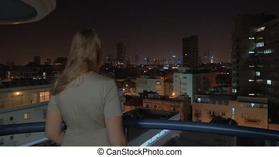 Woman enjoying view of night city from the rooftop. Tel...