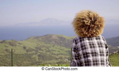 Woman Enjoying View of Ocean and Mountains