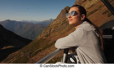 Woman enjoying while riding a cableway - Young brunette ...