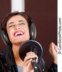 Woman Enjoying While Singing In Studio
