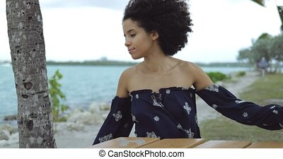 Woman enjoying wind on shoreline - Pretty black woman with...