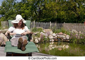 woman enjoys garden pond lies, frau geniesst gartenliege...