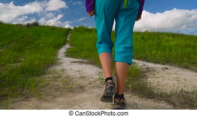 Woman enjoys hiking with a backpack over hilly terrain....