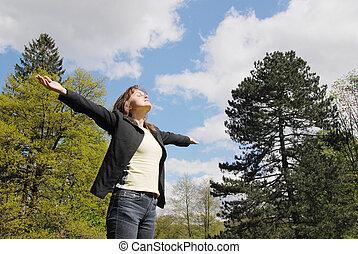 Woman is enjoying her life outdoors among trees on sun