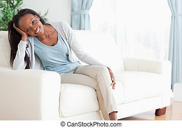 Woman enjoys sitting on the couch