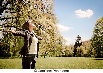 Woman is enjoying her life among trees on spring sun outdoors in park