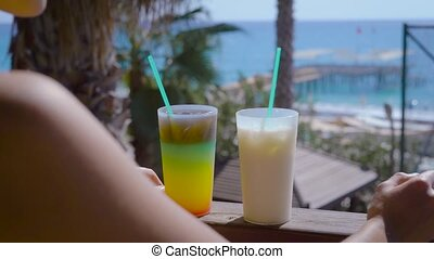 Woman enjoys the view of sea on a terrace with two cocktails