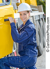 Woman entering cab of heavy goods vehicle