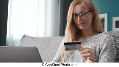 Woman entering data of credit card on laptop for payment