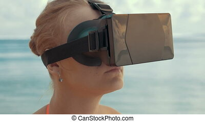 Woman entertaining with VR glasses on the beach