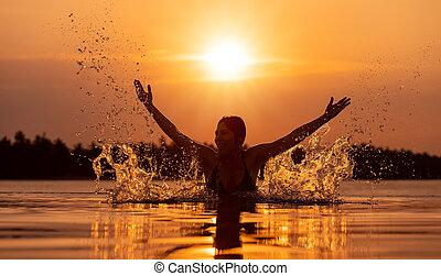 woman enyoying the infinity pool at sunset