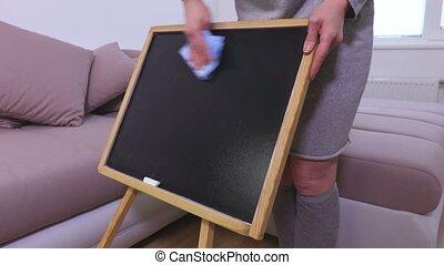 Woman erasing blackboard
