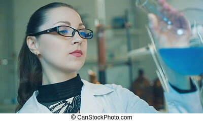 Woman examine flask in a laboratory