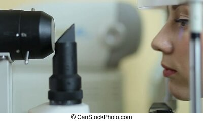 Woman examining eyesight in ophthalmology clinic - Profile...