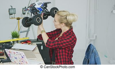 Woman examining radio-controlled car in workshop - Side view...