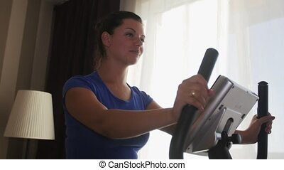 Woman exercising at home with a stationary bicycle.
