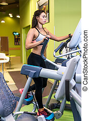 Woman exercising at the gym in an elliptical trainer Cardio training.