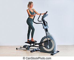 Woman exercising at the gym on crosstrainer