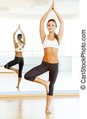 Woman exercising. Full length of beautiful young woman training in aerobics class
