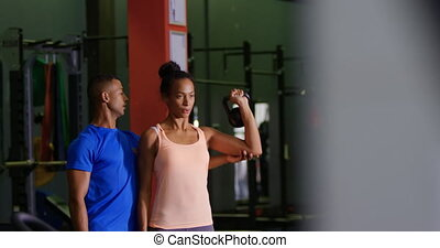 Woman exercising in a gym - Front view of a young mixed race...