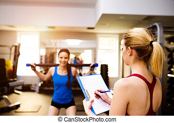 Woman exercising in gym, personal trainer, plan on clipboard