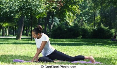 Woman exercising in park on beautiful day. Yoga