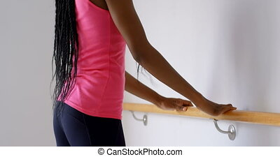 Woman exercising on barre in fitness studio 4k - Young woman...