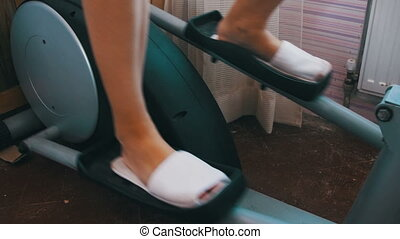 Woman Exercising on the Elliptical Trainer Cross Trainer at Home