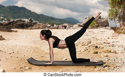 Woman exercising outside on the beach.