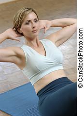 woman exercising - woman doing sit ups on exercise matt