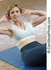 woman exercising - woman doing sit-ups on exercise matt