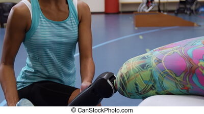 Woman exercising with a prosthetic leg - Low section side...