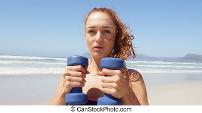 Woman exercising with dumbbells at beach 4k