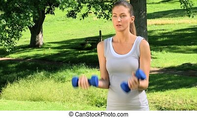 Woman exercising with dumbbells - Athletic woman exercising...