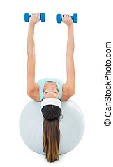 Woman exercising with dumbbells on fitness ball