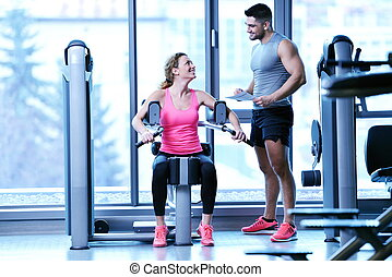 woman exercising with her personal trainer - Gym woman...