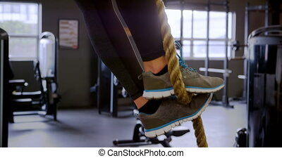 Woman exercising with rope in fitness studio 4k