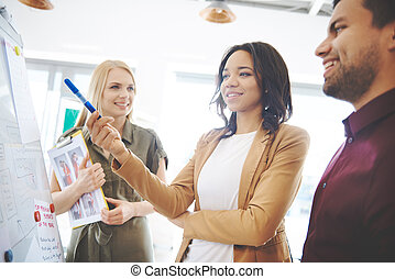 Woman explaining business strategy to coworkers