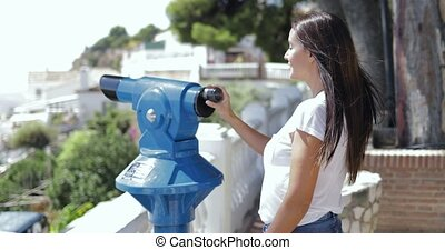 Woman exploring city with spyglass - Side view of young...