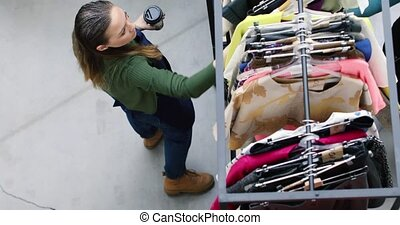 Woman exploring collection of clothes - From above shot of...