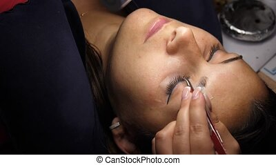 Woman Eye with Long Eyelashes. Eyelash Extension. Lashes, close up, selected focus. Gluing artificial eyelashes with tweezers. Beautician in magnifier glasses performs laborious small work.