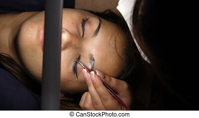 Woman eye with long eyelashes. Eyelash extension. Lashes, close up, selected focus. Gluing artificial eyelashes with tweezers. A woman lies under a lamp on a cosmetic procedure. top view.