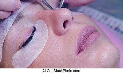 Woman face. Eyelash extension procedure in salon - Close up...