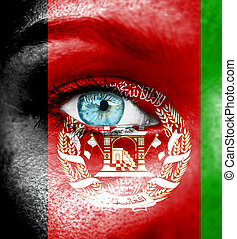 Woman face painted with flag of Afghanistan
