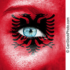 Woman face painted with flag of Albania