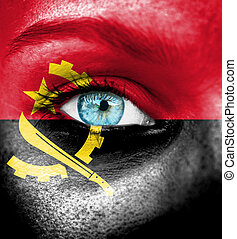 Woman face painted with flag of Angola