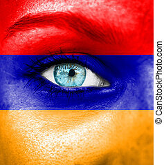 Woman face painted with flag of Armenia