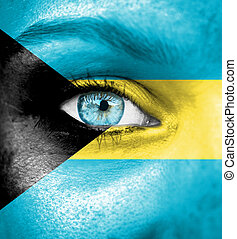Woman face painted with flag of Bahamas