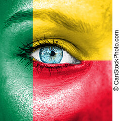 Woman face painted with flag of Benin